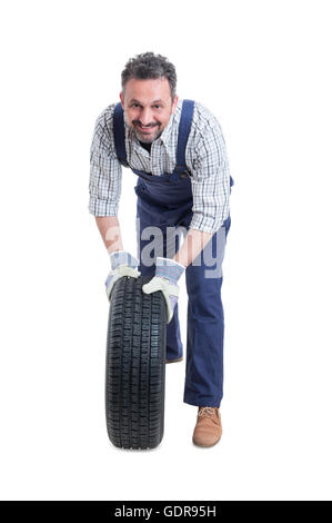 Handsome mechanic in workshop changing car wheel as repair and maintenance concept isolated on white background - Stock Photo