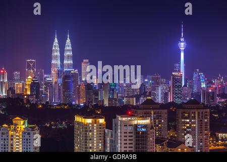 Kuala Lumpur city skyline vibrantly lit at dusk, viewed from west - Stock Photo