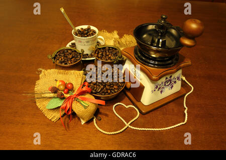 Grinder with coffee beans in copper bowls and Cup with composition of jute - Stock Photo