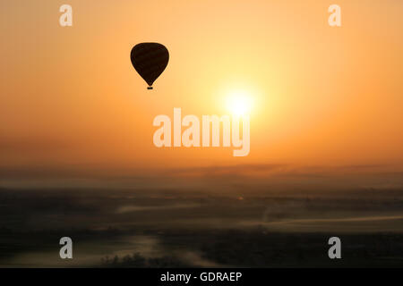 Hot air balloon silhouetted in the  early morning sun during  flight, with foggy patches in the Valley of the Kings, - Stock Photo