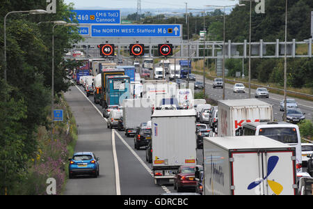 STRANDED VEHICLE WITH TRAFFIC QUEUES AND OVERHEAD GANTRY SPEED SIGNS ON THE NORTHBOUND M6 MOTORWAY BROKEN DOWN CAR - Stock Photo
