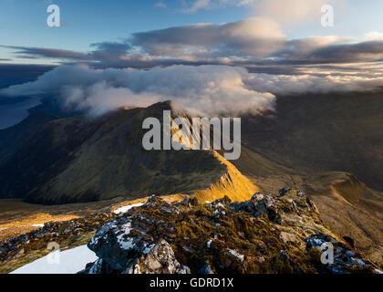 Clouds coming in over the summit of a sidelit Sgur nan Saighead at sunrise - Stock Photo