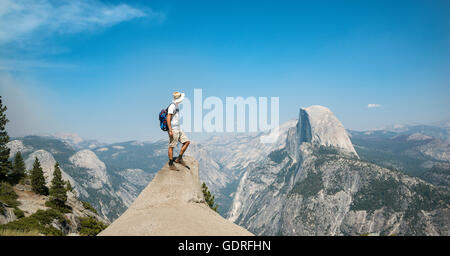 Young man standing on ledge, looking at the Half Dome, view from Glacier Point, Yosemite National Park, California, - Stock Photo