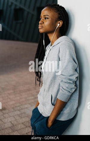 Young woman wearing earphones standing leaning a wall looking away confidently - Stock Photo