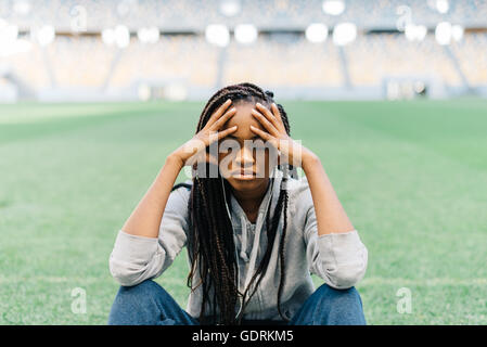 Tired pretty african american young woman sitting with legs crossed and having headache, stadium at background - Stock Photo