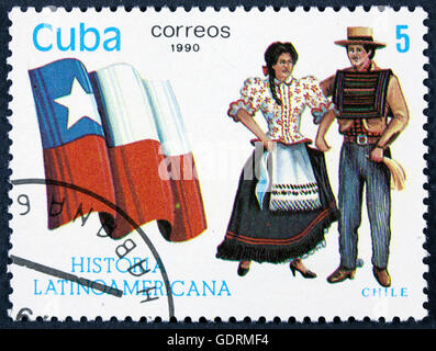CUBA - CIRCA 1990: A stamp printed in Cuba, shows Flag and a couple dressed in national costumes from Colombia, - Stock Photo