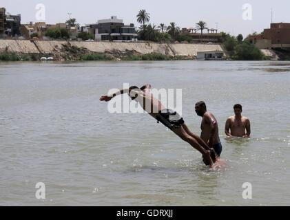 Baghdad, Iraq. 20th July, 2016. An Iraqi man jumps into Tigris river to cool down while temperature reaches above - Stock Photo