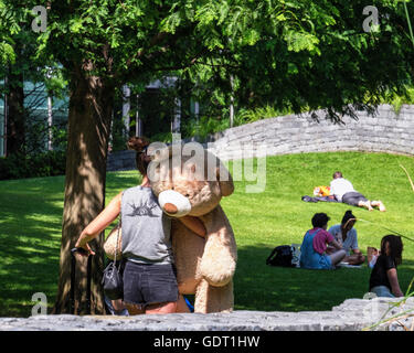 Canary Wharf, London, 20th July 2016. Woman taking teddy bear for a walk. Londoners enjoy the warm Summer sunshine - Stock Photo