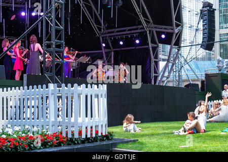 Canary Wharf, London, 20th July 2016. Londoners enjoy the free concert in Canada Square Park. Bankers, office workers - Stock Photo