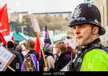 People protest against the coalition Government cuts as a policeman looks on. - Stock Photo