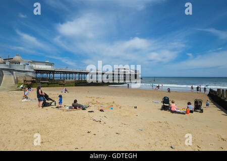 People relaxing on the beach next to Cromer Pier in Norfolk - Stock Photo