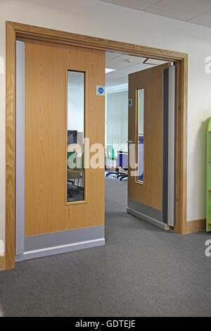 Double fire doors in a modern London School. Doors feature sound-proof bars at & Closed fire doors in a London school corridor UK. Shows glazed ... pezcame.com