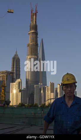 A worker walk at a construction site near the Bund with Pudong's financial area in the background - Stock Photo