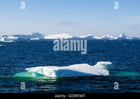 Iceberg floating out to sea ocean above Arctic Circle from Ilulissat Icefjord's Sermeq Kujalleq glacier in summer - Stock Photo