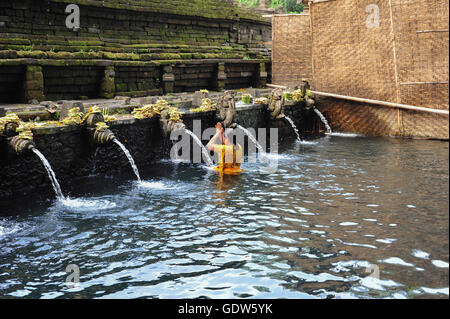 A woman bathing and praying in the fountain of holy water of Tirta Empul Temple in Bali, Indonesia - Stock Photo