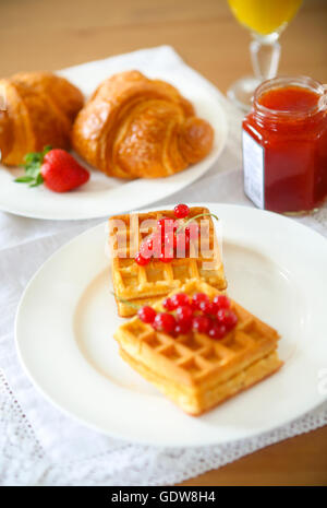 Waffles with red currant jam and berries on a white plate, croissants, orange juice on the wooden background - Stock Photo