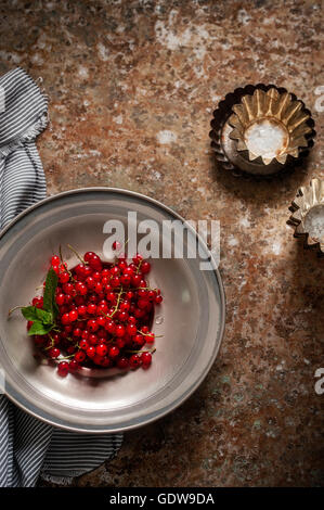 Red currants in muffin tins - Stock Photo