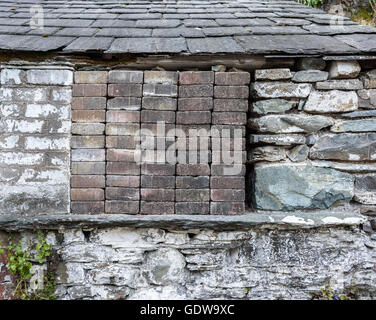 An old barn window blocked out with small bricks. - Stock Photo