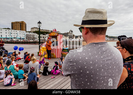 People Watch A Traditional Punch and Judy Show On Hastings Pier, Hastings, Sussex, UK - Stock Photo