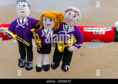 Yarn Bombing decorating public place with knitted objects here the Grimethorpe Colliery Band on Saltburn Pier handrail - Stock Photo