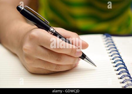 A girl hand is holding a pen and writing on a book - Stock Photo