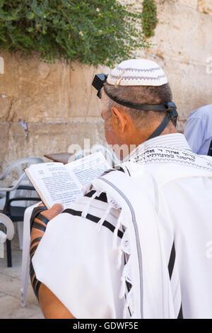 Israel Jerusalem Old City Western Wall religious orthodox Jew Jewish praying wall in Tallit prayer shawl Tefillin - Stock Photo