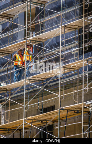 Two workers in bright safety vests standing on scaffolding of tall office building under construction - Stock Photo