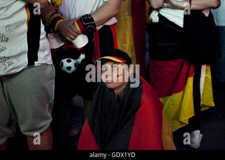 Young woman watches the Germany vs Spain match on the German Fan Mile at the World Cup in Berlin, Germany, 2010 - Stock Photo