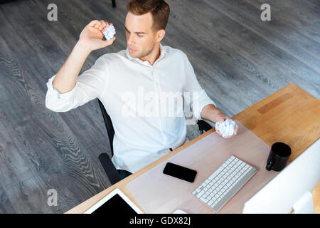 Top view of serious young businessman throwing crumpled paper and working in office - Stock Photo