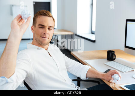 Handsome young businessman crumpling and throwing paper in office - Stock Photo