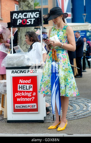 A day at the Races.Woman arriving for Royal Ascot Ladies day next to a Racing Post newspaper stand, Berkshire, England - Stock Photo