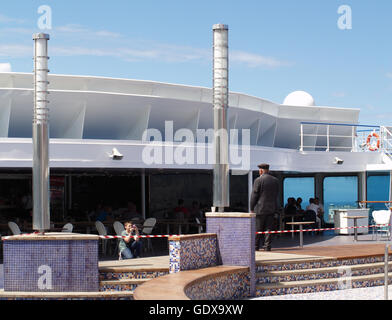 View of passengers in bar area with young boy taking photograph of old manon main deck of Minoan Lines Ferry Cruise - Stock Photo