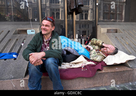 Two homeless men sleeping rough on Whitehall in Central London - Stock Photo