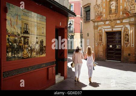 Two young women walk past a large mural of the April Fair 1934, in the Santa Cruz district of Seville, Spain. - Stock Photo
