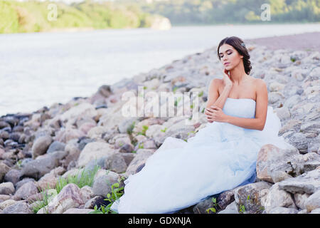 brunette in a lush dress sits on the banks of the river large stones, and spit your face - Stock Photo