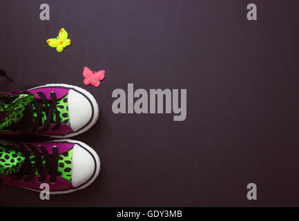 Violet sneakers with leopard print, on black board, vintage filter; copy space - Stock Photo