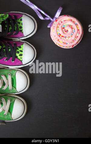 Top view of two pairs of sneakers on black board, with copy space - Stock Photo
