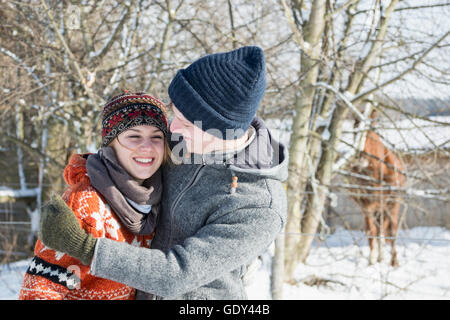 Young couple hugging each other in snow covered landscape, Bavaria, Germany - Stock Photo