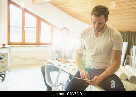 Architect working on digital tablet with his Colleague in background, Bavaria, Germany - Stock Photo