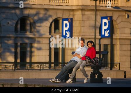 Poelaert square, Marolles neighborhood, Brussels, Belgium. A romantic couple sitting on a bench in the square next - Stock Photo
