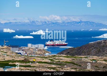 View across dog city to Hurtigruten MS Fram cruise ship moored offshore amongst icebergs in Disko Bay on Arctic west coast. Ilulissat Greenland