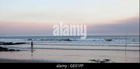 Fisherman fishing on beach during dusk, Viana do Castelo, Norte Region, Portugal - Stock Photo