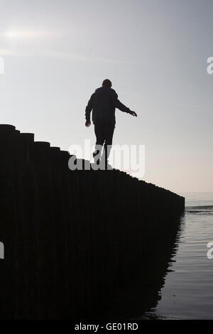 Silhouette of a mature man balancing on wooden post at beach, Renesse, Schouwen-Duiveland, Zeeland, Netherlands - Stock Photo