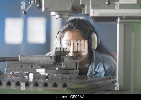 Young female engineer wearing headphones and working in an industrial plant, Freiburg im Breisgau, Baden-Württemberg, - Stock Photo