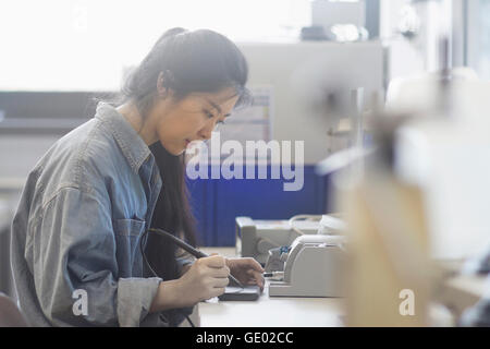 Female technician soldering electronic components in an industrial plant, Freiburg Im Breisgau, Baden-württemberg, - Stock Photo