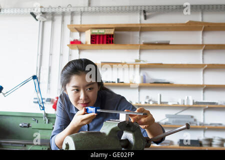 Young female engineer grinding metal in an industrial plant, Freiburg im Breisgau, Baden-Württemberg, Germany - Stock Photo
