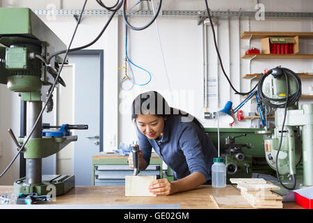 Young female carpenter sawing a piece of wood in an industrial plant, Freiburg im Breisgau, Baden-Württemberg, Germany - Stock Photo