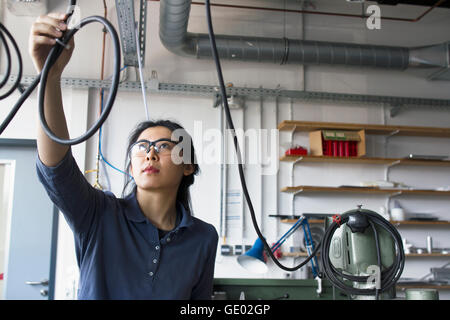 Young female engineer checking cables in an industrial plant, Freiburg im Breisgau, Baden-Württemberg, Germany - Stock Photo
