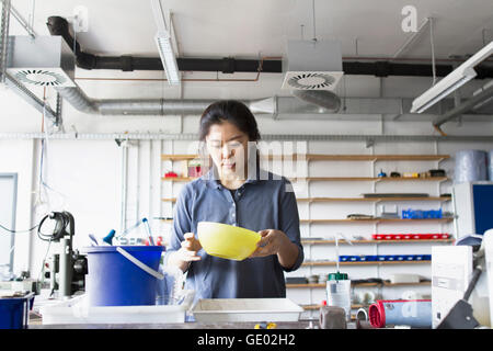 Young female engineer looking into pan in an industrial plant, Freiburg im Breisgau, Baden-Württemberg, Germany - Stock Photo