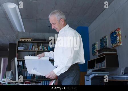 Senior businessman looking at blueprint in the office, Freiburg im Breisgau, Baden-Württemberg, Germany - Stock Photo
